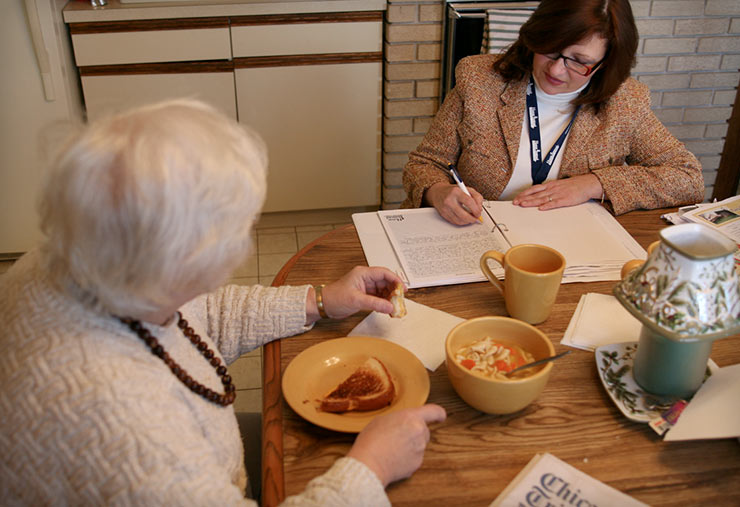 A woman consulting with a senior on paying for care.