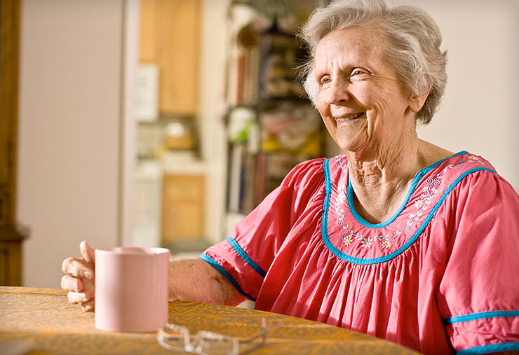 An older woman enjoying her morning coffee.