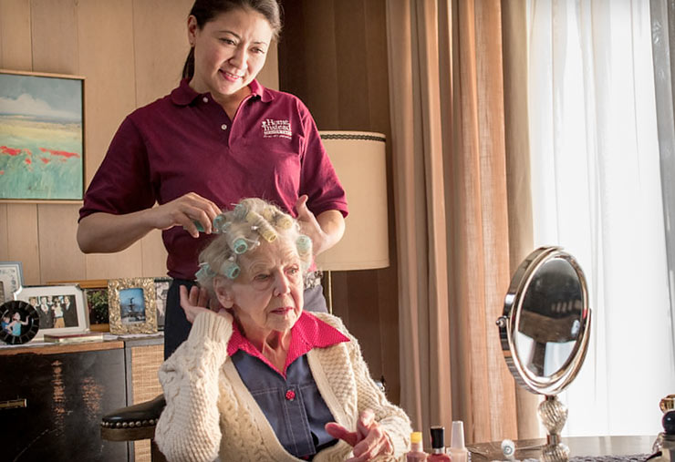 A Home Instead CAREGiver styles the hair of a senior woman.