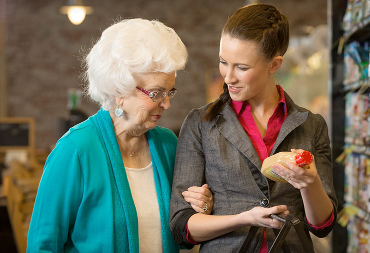 A woman helps a senior with her shopping.
