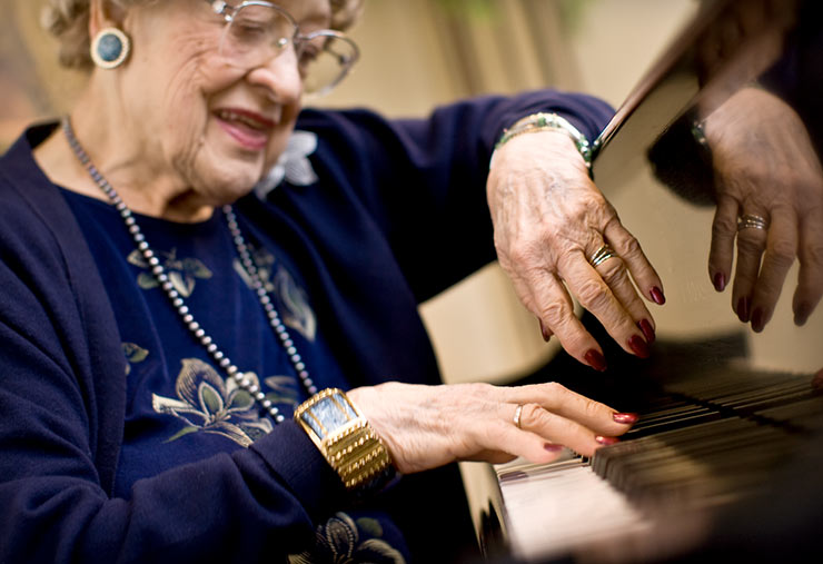 A senior happily plays her piano.