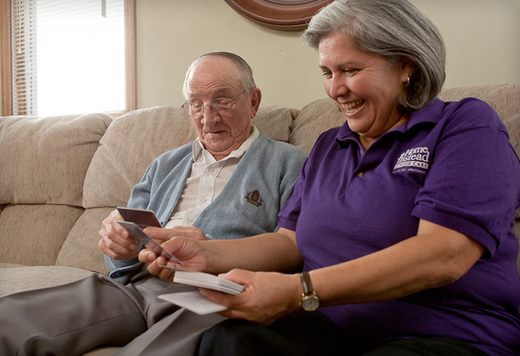 A caregiver interacting with an older man.