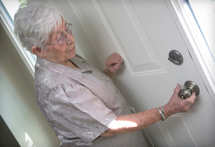A senior woman tries to open her front door.